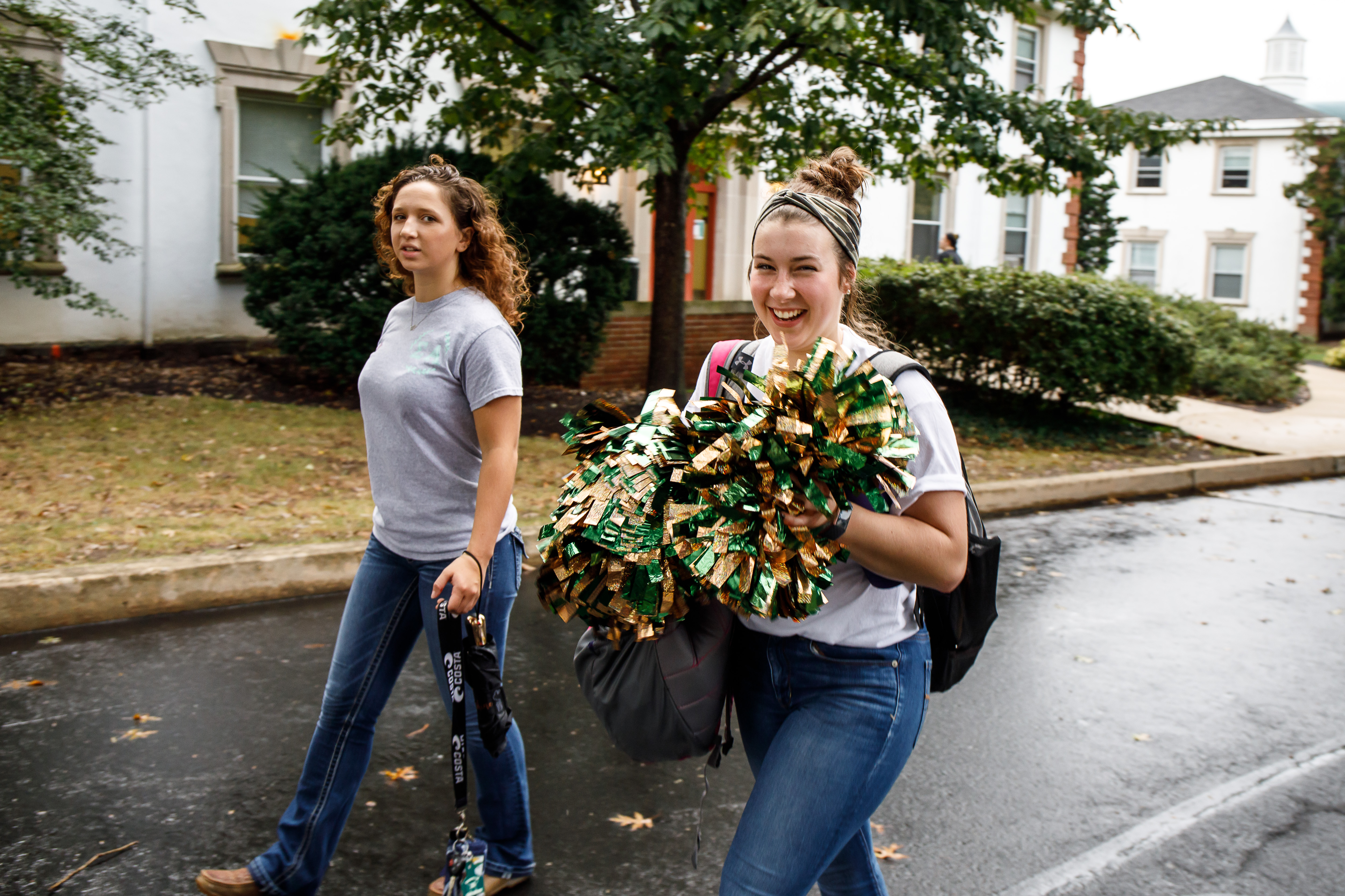 Students walking on DelVal's campus with pompoms