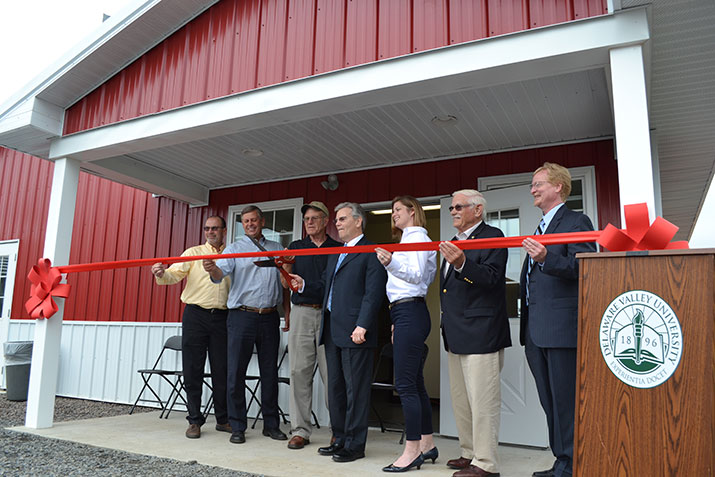 A group of people cuts a red ribbon to celebrate the opening of the swine science center.