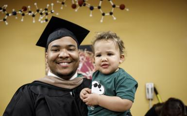 A graduate from the Continuing Studies department in his cap and gown, holding his son.