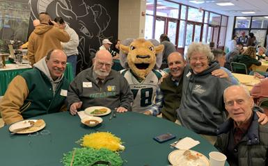 Older alumni sitting around a table with the DelVal mascot.