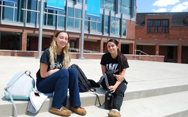 Two female students sitting on the steps of the campus on a sunny day