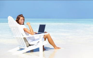 Young woman sitting in chair on beach with a laptop computer on her lap