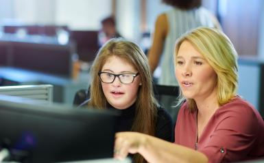 Female teacher with teenage girl with Down Syndrome working together at a computer.