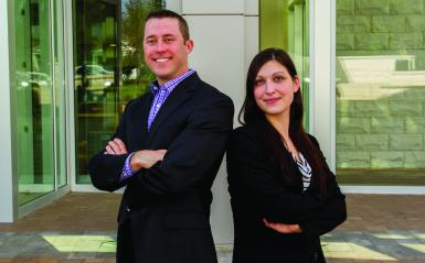 Professional looking 30-something man and woman standing back to back and smiling at camera.