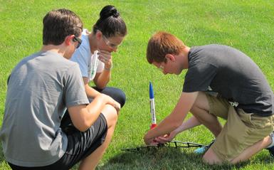 three students prepping a model rocket on the lawn