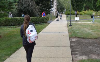 A student is walking on a scenic campus path wearing a backpack.
