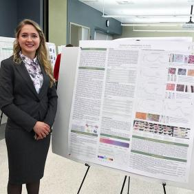 Diana Rachii, who is wearing a grey suit, stands in front of a scientific research poster. The poster is about her research on fruit pigments.