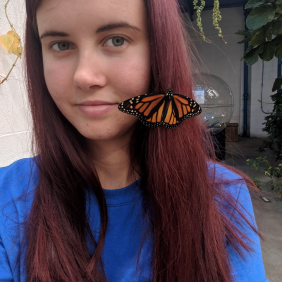 Arianna Logan poses outdoors with a butterfly