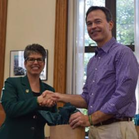 Dr. Charles Heise shakes hands with DelVal President Dr. Maria Gallo.
