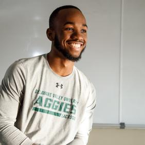 Khalil Lindsey smiling and wearing an Aggies shirt.