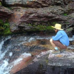 Student Zac Haynes kneeling near waterfall.