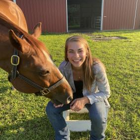 Delaware Valley University animal science student Jalene Beach next to a horse.