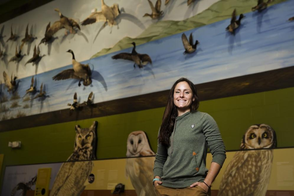 Lauren Fenstermacher, a DelVal alumna, poses for a photograph in front of a wall with birds at Middle Creek Wildlife Management Area.