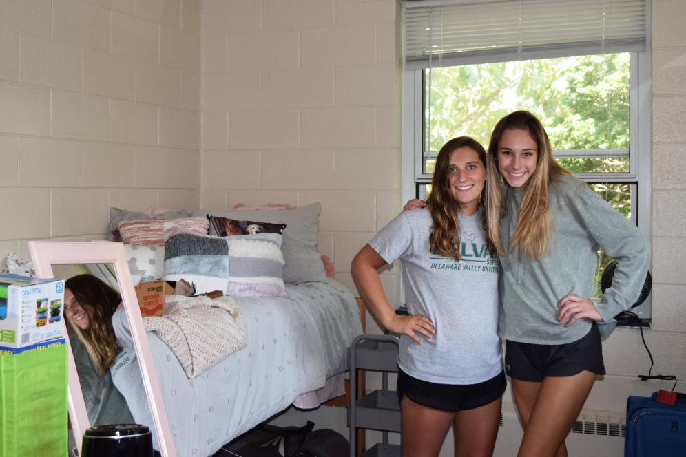 Two female students smiling in a dorm.