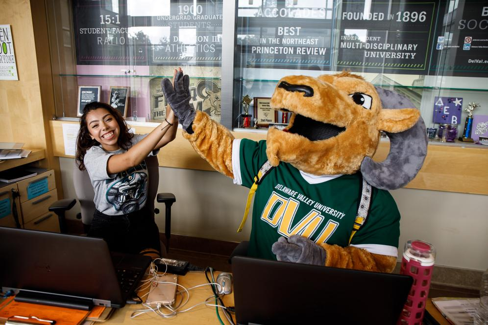 Mascot giving a high five to sitting student.