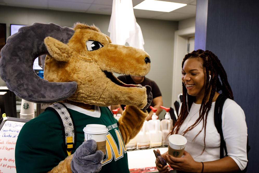 A student and the mascot grab a drink from Starbucks.