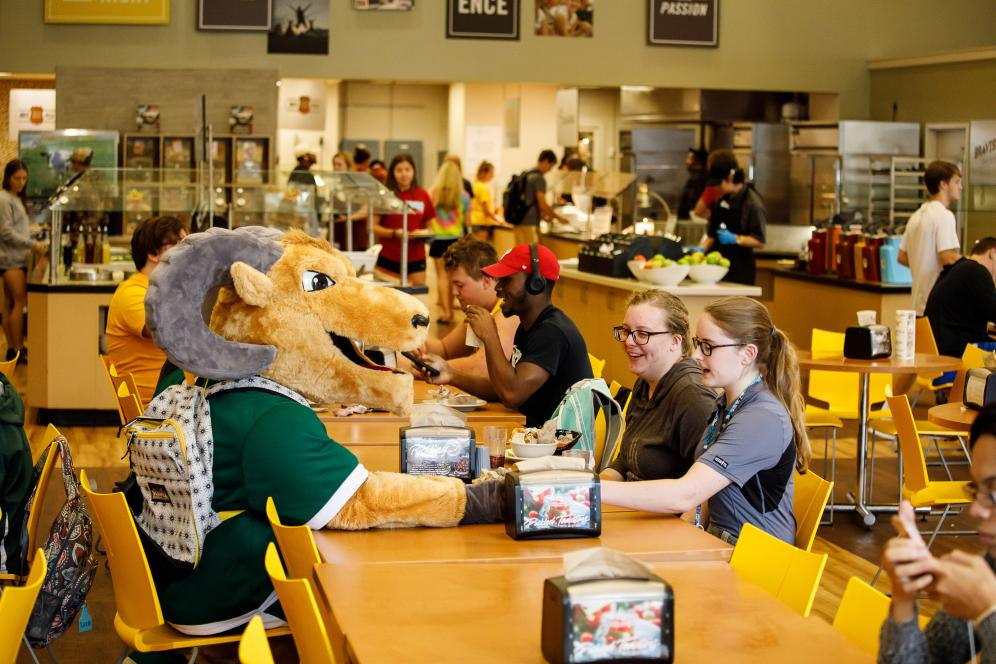 The mascot sitting at the lunch table with two students.