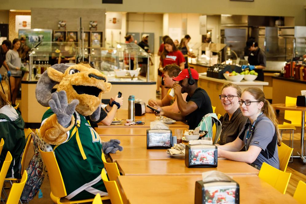 The mascot waving while in the dining hall.