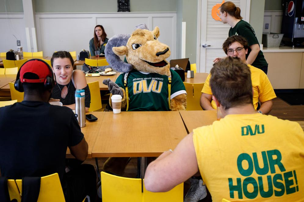 School mascot surrounded by students at lunchtable.