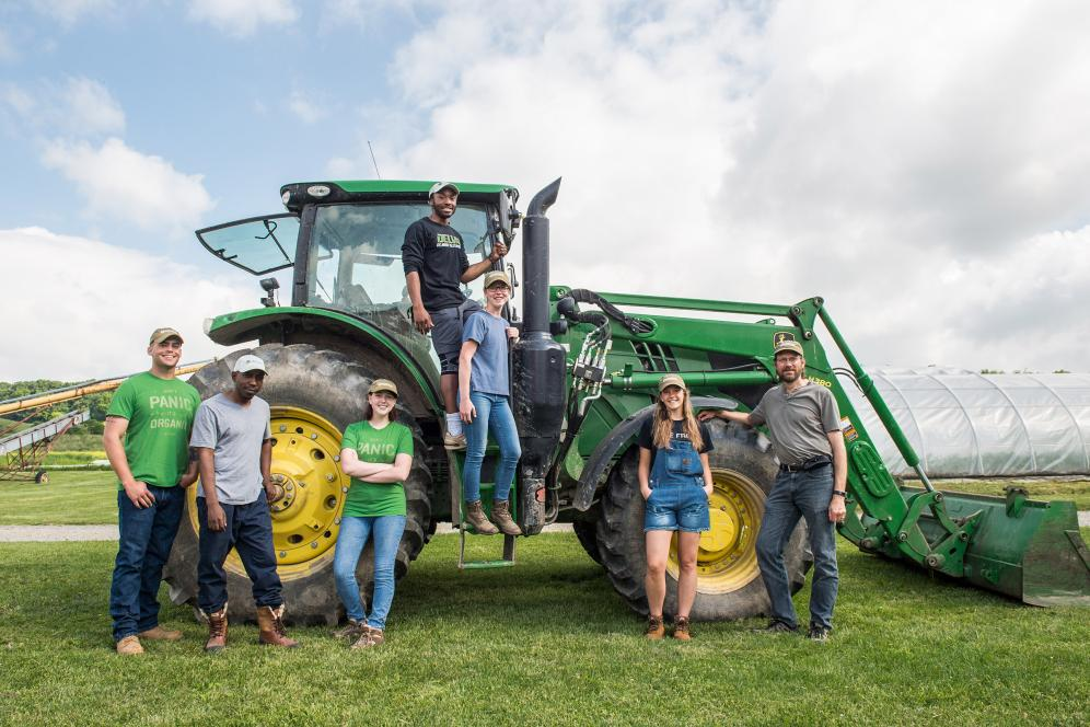group of students posing on and with a tractor