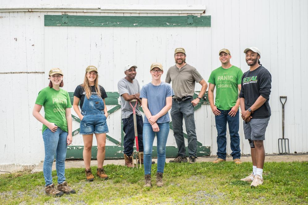 group of students posing outside of a barn