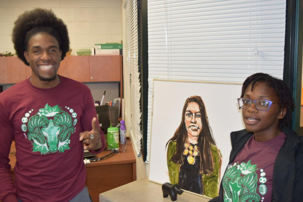 student and staff member posing next to art in the multicultural lounge.