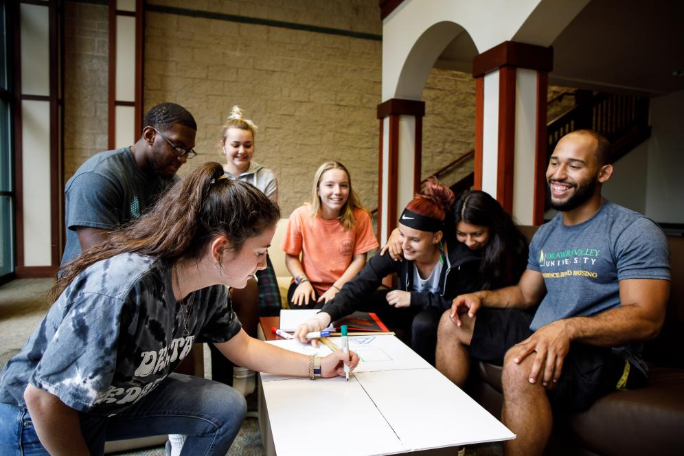 A group of students gathered around a posterboard writing.