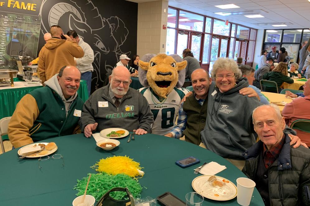 A group of alumni sitting around a table with the mascot.