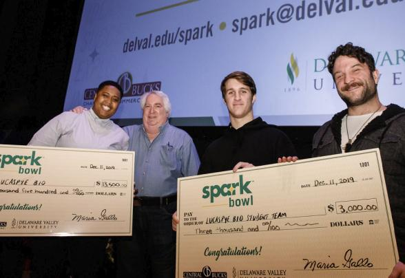 Four people standing on a stage with holding two prize money checks won from DVU's Spark Bowl business competition.
