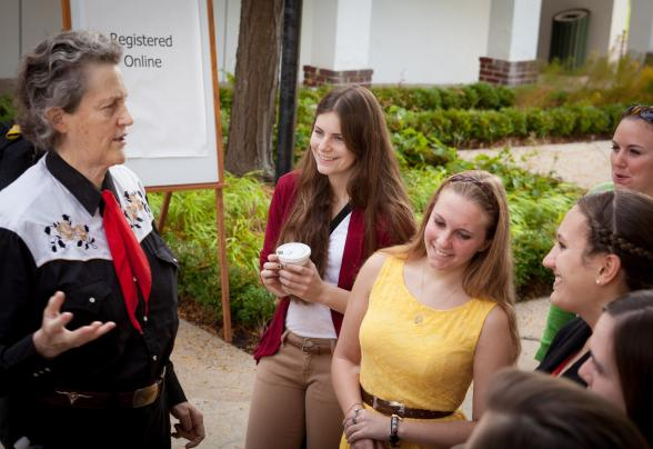Dr. Temple Grandin stands outside talking with DVU students.