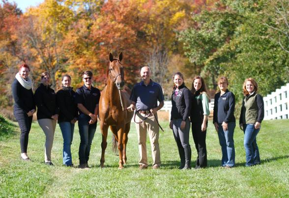 Students and faculty member standing with horse in a field