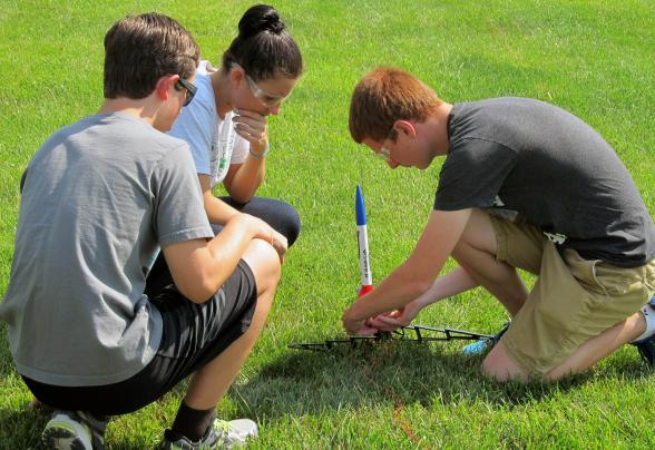 Three students launching a rocket on campus