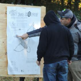 A conservation wildlife officer pointing to a goose poster with a student