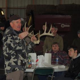A man holds up deer antlers to a group of students