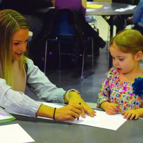 female student drawing with child