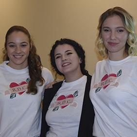 Three students standing together wearing shirts that have their business logo on the front.