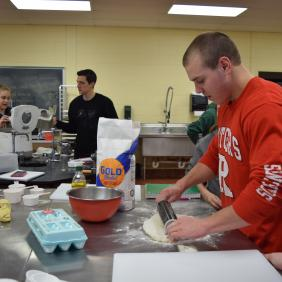 A student rolling out dough in the food lab