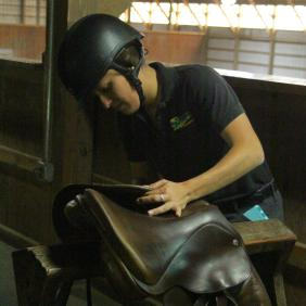 Student adjusting a saddle in the barn