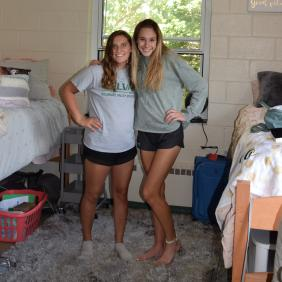 Two female students in their dorm room with arms around each other smiling.
