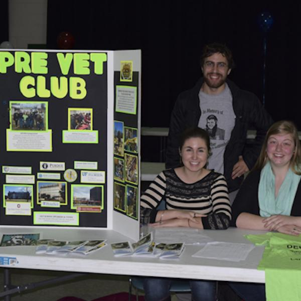 a group of students behind a table with pre-vet club materials