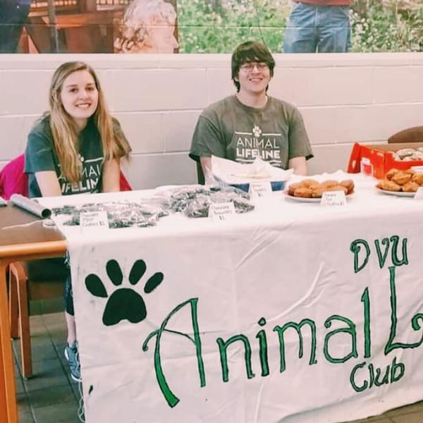 Two students sit at the animal lifeline club table at an activities fair.