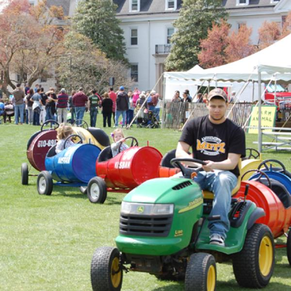 A student driving a lawn mower pulling train cars with passengers