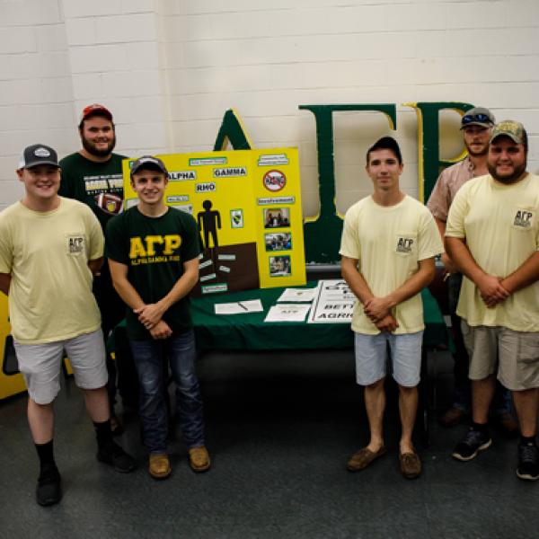 Alpha Gamma Rho students stand in front of their activities fair table