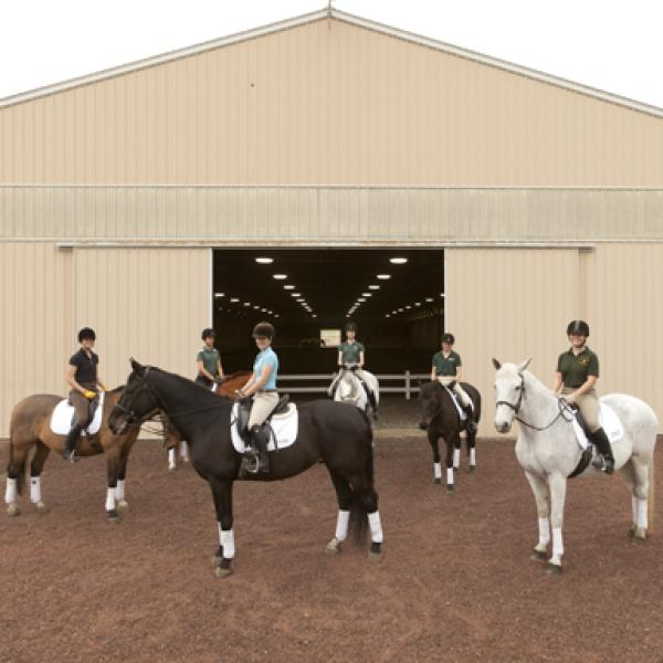 A group of students sit on dressage horses outside of a barn