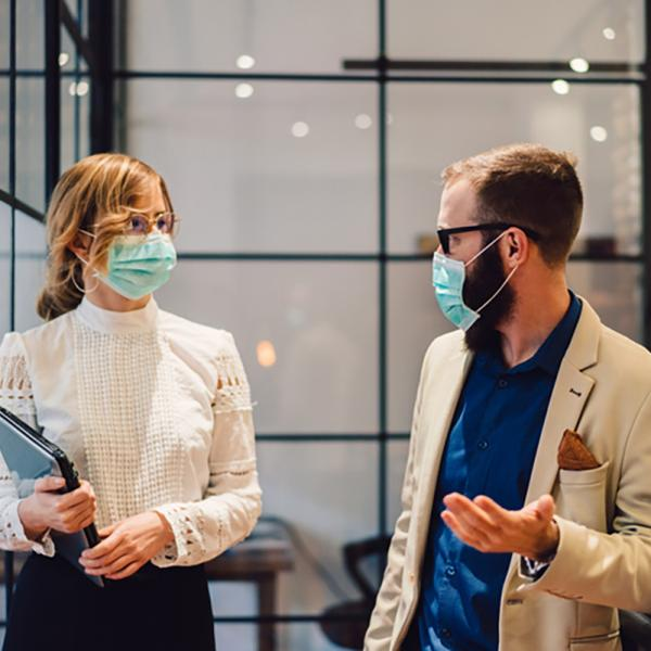 Two hospital administrators speaking in a hallway, both wearing protective masks.