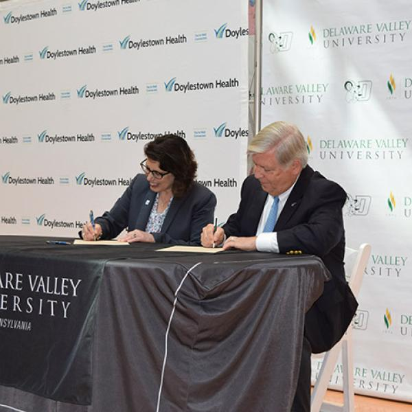 Officials sign an agreement between DelVal and Doylestown Health