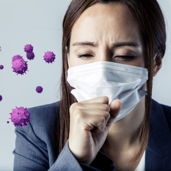 A woman wearing a mask and coughing, purple virus is in the air.