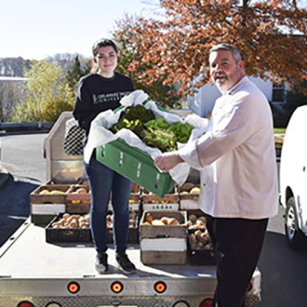 Student and teacher delivering lettuce and vegetables