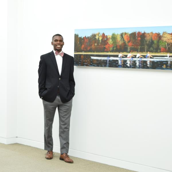 A business student standing next to a painting on the wall.