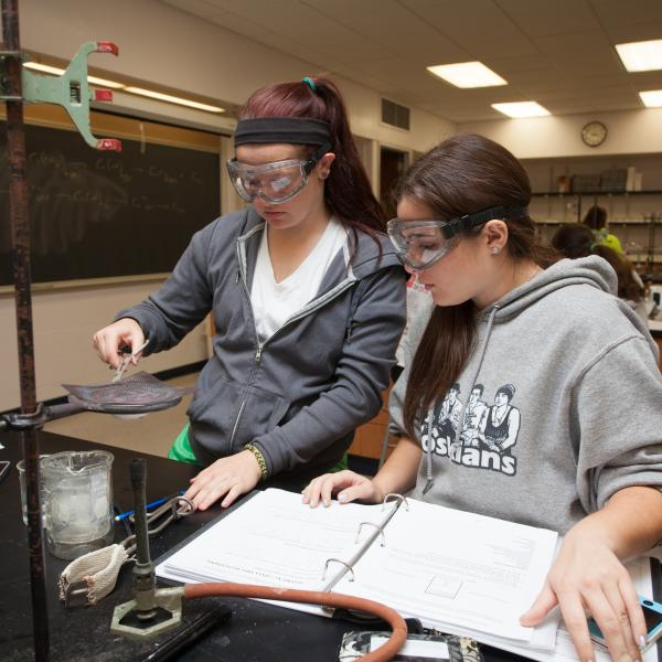 Two lab partered students using scientific equipment.